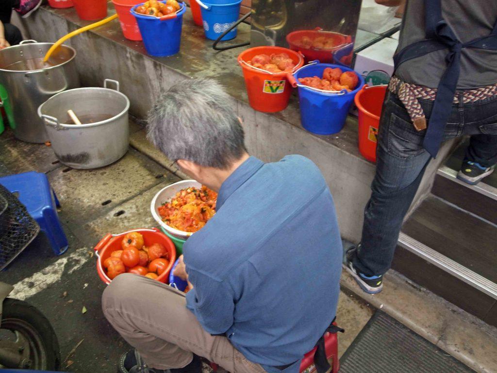 トマト牛肉面で有名な甘記蕃茄刀削麺のトマトを剥いているおじさんの写真